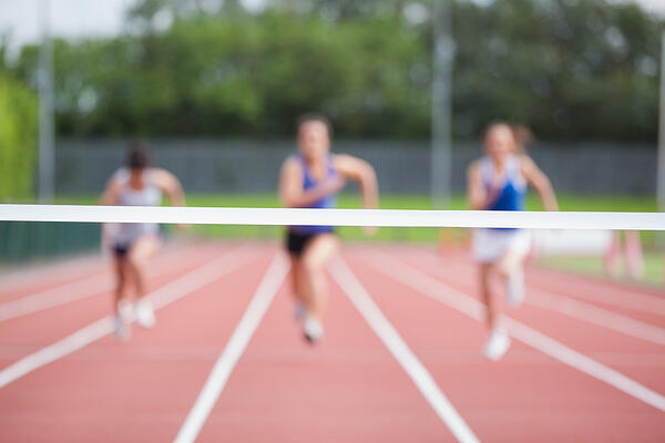 Female athletes running towards finish line on track field-1