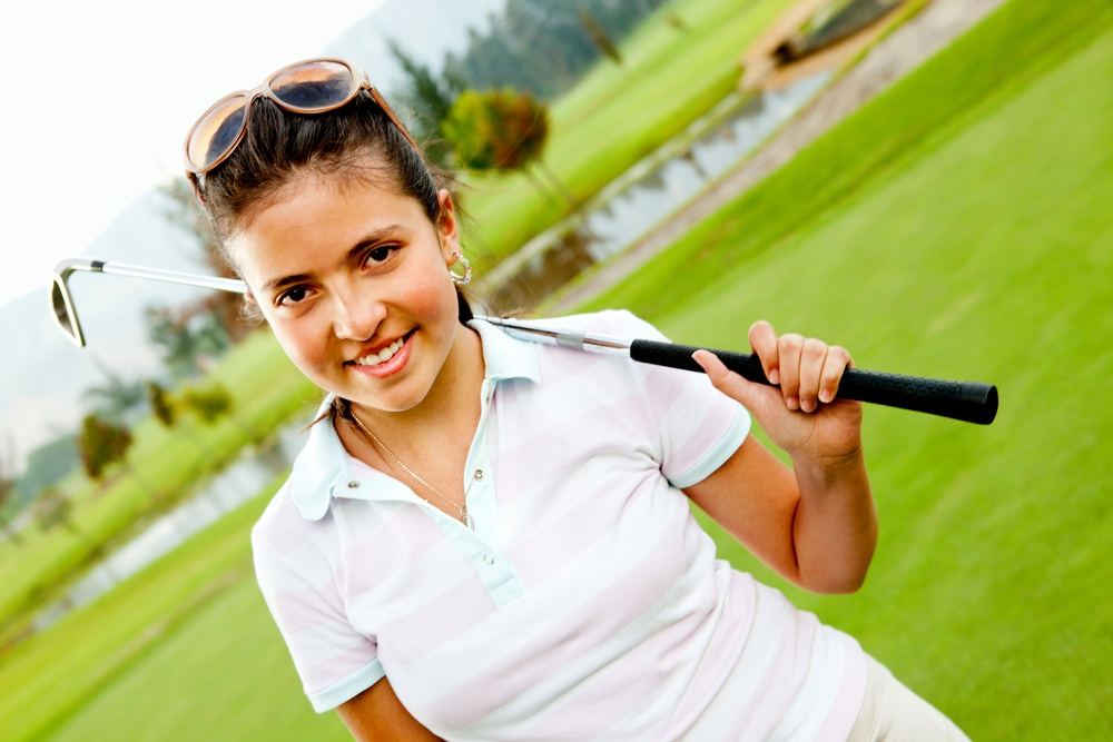 Girl at the course playing golf and holding a club