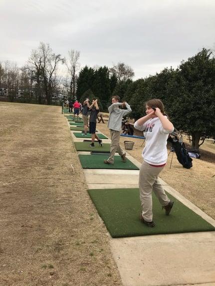 golf team practice swinging golf clubs