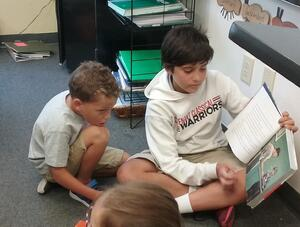 middle school student reading young child